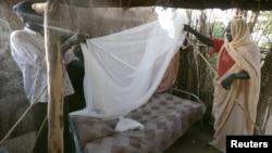 Perempuan Sudan menerima bantuan mendirikan kelambu.