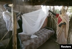 FILE - A Sudanese women gets help setting up a bed net.