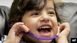 Bé gái cười trong khi được kiểm tra thính giác. (Ảnh tư liệu)
