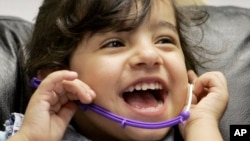 FILE - Three-year-old Amina of Iraq laughs during a hearing test. The WHO reports 360 million people around the globe suffer from disabling hearing loss and that nearly 32 million are children.