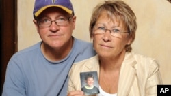 FILE - Patty and Jerry Wetterling show a photo of their son Jacob Wetterling, who was abducted in October of 1989 in St. Joseph, Minn., and is still missing, in Minneapolis, Aug. 28, 2009. Patty Wetterling said Saturday that Jacob's remains have been foun