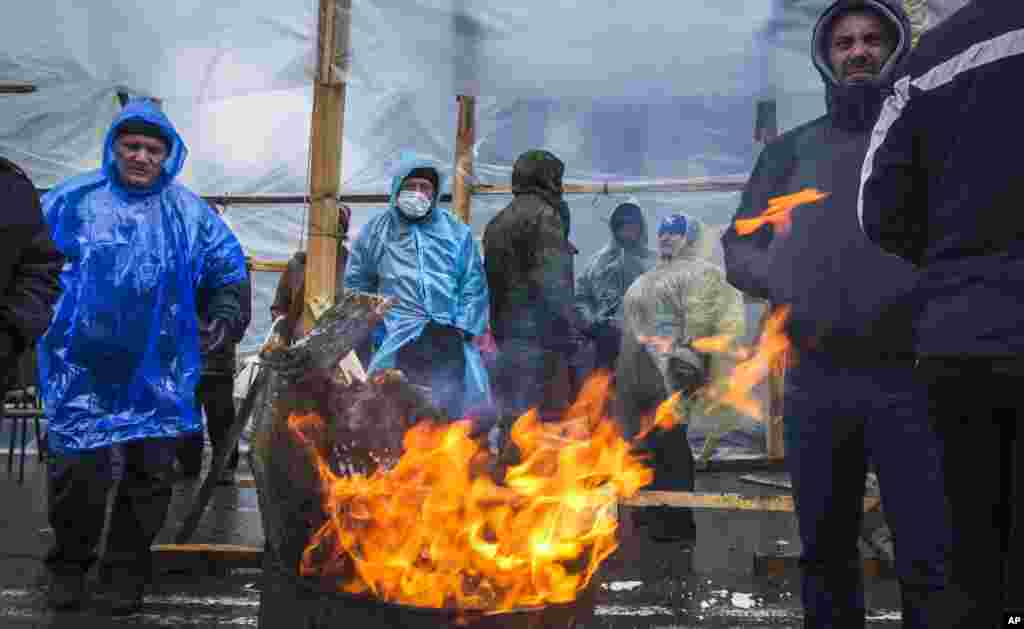 A group of pro-Russian activists warm themselves at a bonfire next to barricades in front of an entrance to the Ukrainian regional office of the Security Service in Luhansk, Ukraine, April 11, 2014.