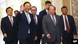 Chinese State Councilor Yang Jiechi, front left, waves as he arrives with Cambodian Deputy Prime Minister and Foreign Minister Hor Namhong, front right, for their meeting at Diaoyutai State Guesthouse in Beijing Thursday, Feb. 4, 2016. (How Hwee Young/Pool Photo via AP)