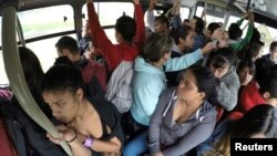 FILE - Passengers ride a Transmilenio system bus during rush hour in Bogota, October 27, 2014.