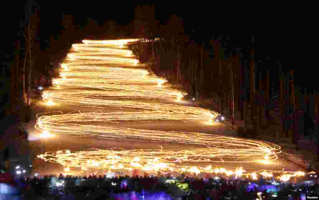Spectators (bottom) watch skiers descending down from the slope while holding lit torches during an annual winter torch festival in the town of Zheleznogorsk, some 50km (31 miles) northeast of Russia's Siberian city of Krasnoyarsk.