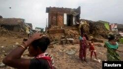 Cư dân làng chài đứng trước nhà cửa bị hư hại vì bão tại bang Odisha ở miền đông Ấn Độ, ngày 14/10/2013.