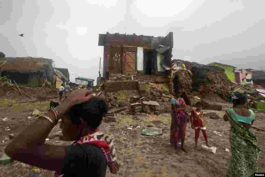 Fisherwomen and a girl stand in front of damaged house after Cyclone Phailin hit Puri in the eastern Indian state of Odisha, Oct. 14, 2013.