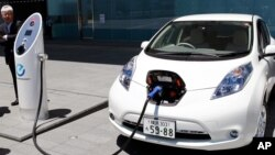 FILE - А Nissan Leaf is getting a quick charge by a solar-assisted EV charging system at Nissan's global headquarters in Yokohama, Japan, July 11, 2015.