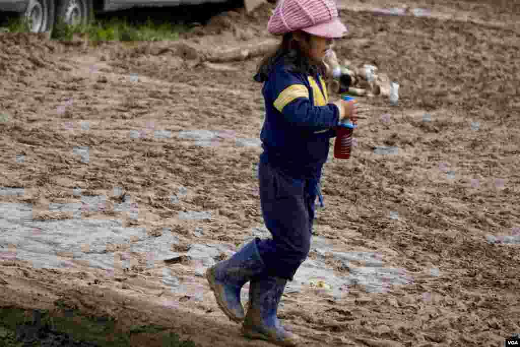 Seorang anak perempuan Suriah berjalan melintasi tanah berlumpur. (VOA/Jamie Dettmer)