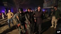 2014年1月17日,阿富汗首都喀布尔一家餐馆发生爆炸后,安全警卫协助现场受害人员前往医院治疗