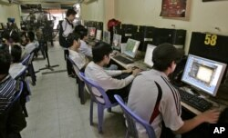 FILE - Students surf web at an Internet cafe in Hanoi, Vietnam, March 31, 2010.
