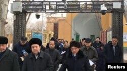 Para Imam dan warga Muslim Uighur melewati kamera keamanan yang dipasang pemerintah China saat keluar dari Masjid Id Kah di kota Kashgar, Xinjiang, China (foto: dok).