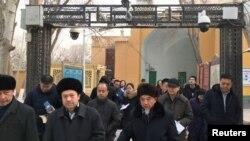 Các giáo sĩ và giới chức qua lại dưới giàn camera an ninh vào lúc rời đền thờ Hồi giáo Id Kah trong một chuyến đi thăm do Bắc Kinh tổ chức tới vùng Tân Cương. Ảnh chụp ngày 4/1/2019.