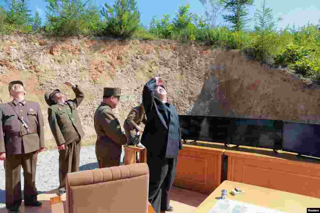 북한의 김정은 국무위원장이 발사된 '화성-14형'을 올려다보고 있다.