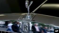FILE - Pedestrians are reflected in the chrome work under the Spirit of Ecstasy on the front of a Rolls- Royce luxury automobile, in a show room in London, July 8, 2014.