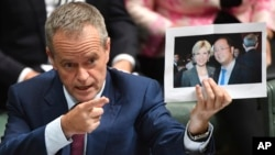 Leader of the opposition party Bill Shorten holds a photograph of Minister for Foreign Affairs Julie Bishop and Chinese businessman Huang Xiangmo, June 14, 2017, in Canberra, Australia. Australia has canceled the residency of Huang.