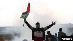 가자 지구에서 반이스라엘 시위 중 참가자가 팔레스타인 국기를 들고 소리치고 있다.