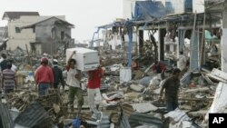Para penyintas di tengah puing-puing akibat tsunami di Banda Aceh, 31 Desember 2004.