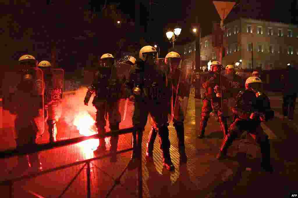 Cảnh sát chống bạo loạn bị tấn công bằng hỏa pháo trước trụ sở Quốc hội ở Athens, 19 tháng 2, 2012. (AP)