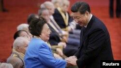 中国国家主席习近平在纪念中国抗日战争胜利60周年的一次颁奖仪式上与飞虎队将军陈纳德的遗孀陈香梅握手。(2015年9月2日)