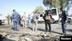 Pasukan keamanan Irak memeriksa lokasi serangan bom bunuh diri di Kut, 150 kilometer sebelah tenggara Baghdad (30/9). Serangan ini menewaskan sedikitnya 4 polisi setempat.