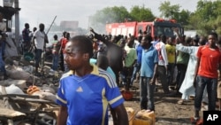 FILE - People gather at the scene of a car bomb explosion in Maiduguri, Nigeria, July 1, 2014. Residents blamed Boko Haram for the attack.