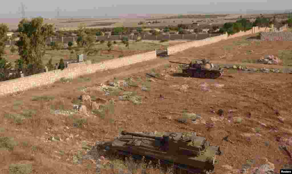 Tanks belonging to forces loyal to Syria's President Bashar al-Assad are seen in al-Mansoura in the Aleppo countryside, June 2, 2013.