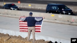 David Morgan of Highlands Ranch, Colo., holds an American flag as a procession of law enforcement vehicles accompany a hearse carrying the body of a sheriff's deputy shot and killed while responding to a domestic disturbance, Dec. 31, 2017, in Highlands R