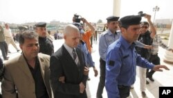 Iraqi policemen escort British security contractor, Danny Fitzsimons, outside a court in Baghdad, February 28, 2011