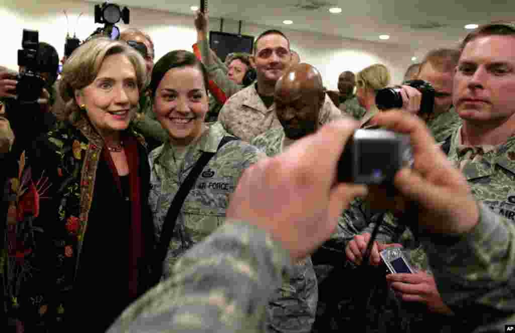 Clinton poses with U.S. Army soldiers during a brief visit to the U.S. camp at the military airport in Kabul, Afghanistan, November 19, 2009. Clinton visited to attend the inauguration of President Hamid Karzai.