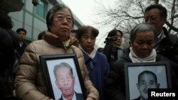 26일 중국인 강제 징용 피해자들이 일본 기업들을 대상으로 무더기 손해배상 청구소송을 낸 가운데, 유가족들이 피해자들 초상화를 들고 베이징 법원 앞에 서 있다.