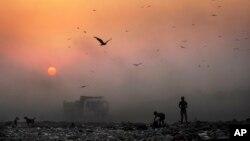Asap tebal terlihat di angkasa sementara anak-anak pemulung mencari barang yang bisa didaur ulang di tempat pembuangan sampah di New Delhi, India. (Foto: Dok)