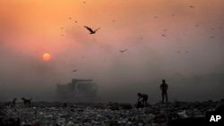 FILE- A thick blanket of smoke is seen against the setting sun as young ragpickers search for reusable material at a garbage dump in New Delhi, India.