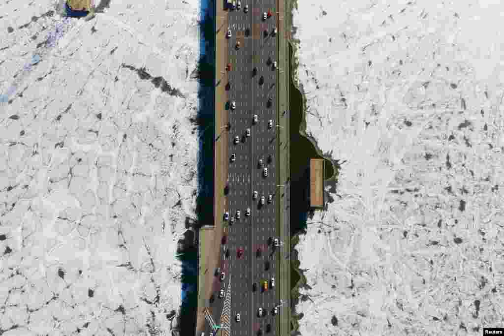 Vehicles travel on a bridge over the partially frozen Hun river in Shenyang, Liaoning province, China, Dec. 25, 2018.