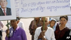 "Sam Souen, an 86 year-old Cambodian woman, holds a banner asking Prime Minister Hun Sen, seen in photo at left, to help solve the problem of land grabbing, which reads ""We have been victimized by land grabbing in Banteay Meanchey province"" as she and othe"