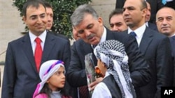 Turkey's President Abdullah Gul, center, is welcomed by children in local traditional dress, at the airport in Diyarbakir, Turkey, 30 Dec 2010