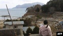 Bé Kon Manami, 4 tuổi, ngồi chờ cha mẹ và em gái vẫn còn bị mất tích sau thảm họa động đất và sóng thần ở Miyako, phía Bắc Nhật Bản