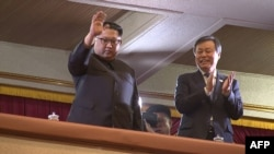 This picture captured from video footage by Korea Pool reporters shows North Korean leader Kim Jong Un (L) and South Korea's Culture, Sports and Tourism Minister Do Jong-whan (R) during a rare concert by South Korean musicians at the 1,500-seat East Pyongyang Grand Theater in Pyongyang, North Korea, April 1, 2018.