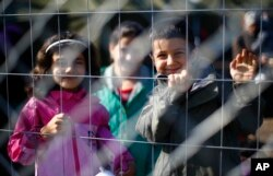 FILE - Children behind a fence in a temporary holding center for migrants near the border line between Serbia and Hungary in Roszke, southern Hungary in Roszke, Sept. 12, 2015.