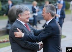 FILE - Ukrainian President Petro Poroshenko, left, and NATO Secretary General Jens Stoltenberg, shake hands during a meeting in Kyiv, Ukraine, July 10, 2017.