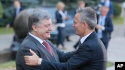 Ukrainian President, Petro Poroshenko, left, and NATO Secretary General Jens Stoltenberg, shake hands during a meeting in Kiev, Ukraine, July 10, 2017.