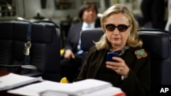 FILE - In this Oct. 18, 2011, photo, then-secretary of state Hillary Clinton checks her smartphone aboard a C-17 military plane en route to Tripoli, Libya. Clinton's handling of emails has figured prominently in the presidential campaign.