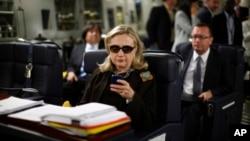 (Ảnh tư liệu) - Trong bức ảnh chụp hồi tháng 10, 2011, bà Clinton lúc đó là Ngoại trưởng Hoa Kỳ kiểm tra điện thoại khi ở bên trong máy bay quân sự C-17 trên đường bay từ Malta tới Tripoli, Libya.