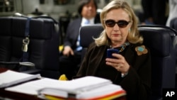 FILE - In this Oct. 18, 2011, file photo, then-secretary of state Hillary Clinton checks her Blackberry from a desk inside a C-17 military plane.