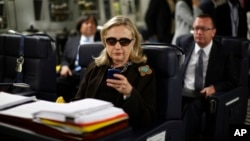 FILE - In this Oct. 18, 2011, file photo, then-Secretary of State Hillary Rodham Clinton checks her Blackberry from a desk inside a C-17 military plane upon her departure from Malta, in the Mediterranean Sea, bound for Tripoli, Libya.