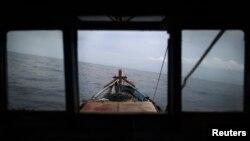 Nelayan Rusli Suhardi mengarahkan kapalnya ke wilayah pencairan ikan di pantai Natuna Besar, 9 Juli 2014. (Foto: Reuters)