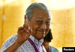 Mahathir Mohamad, former Malaysian prime minister and opposition candidate for Pakatan Harapan (Alliance of Hope), holds up an ink-stained finger as he votes during the general election in Alor Setar, Malaysia, May 9, 2018.