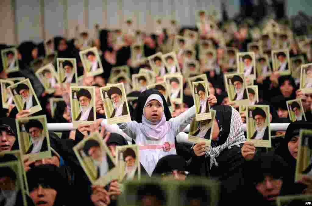 Fotografia disponibilizada na página oficial do Líder Supremo iraniano Ayatollah Ali Khamenei. Mostra mulheres iranianas e uma menina com retratos seus durante uma reunião no Teerão.