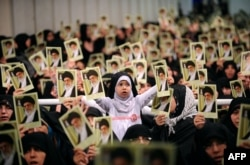 Picture released by the official website of Iranian Supreme Leader Ayatollah Ali Khamenei shows Iranian women and a girl holding up portraits of him during a meeting in Tehran, Feb. 17, 2014.