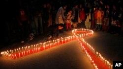 """Perempuan dan anak-anak Nepal dari """"Maiti Nepal"""", pusat rehabilitasi korban perdagangan seks, menyalakan lilin berbentuk pita merah malam menjelang peringatan Hari AIDS Sedunia yang jatuh setiap 1 Desember, di Kathmandu. (AP/Niranjan Shrestha)"""